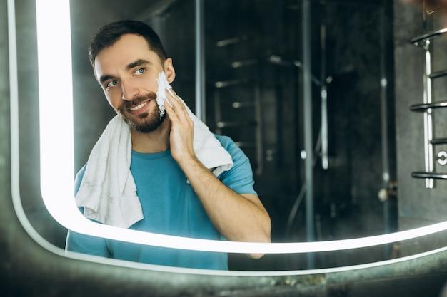 거울 앞에 서서 그의 얼굴 욕실 아침에 보습 크림을 바르는 그의 목에 수건으로 매력적인 젊은 남자의 근접 촬영