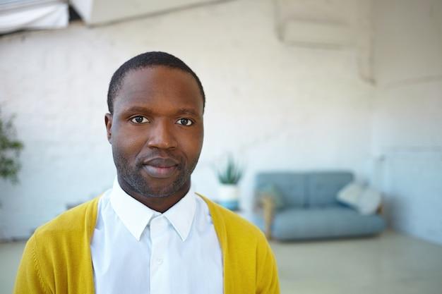 Крупным планом привлекательный молодой небритый афро-американский мужчина в модном желтом кардигане над белой рубашкой, глядя и улыбаясь в камеру, стоя в современной гостиной с диваном в фоновом режиме
