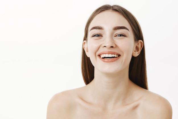 Крупным планом красивая и счастливая молодая очаровательная женщина позирует обнаженной, смеясь и улыбаясь, глядя