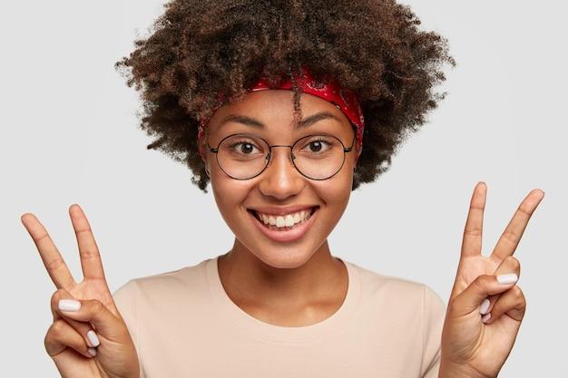巻き毛の美しい陽気な暗い肌の若い女性のクローズアップショットは、両手でピースサインを作ります