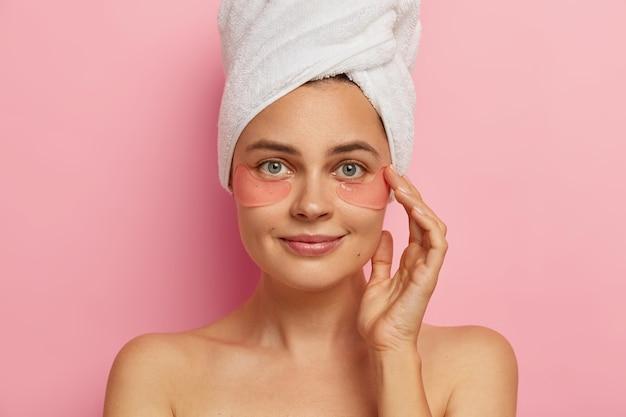 아름다운 유럽 여성 모델의 클로즈업 샷은 샤워 후 스파 절차를 만들고 눈 밑에 콜라겐 패치를 적용하며 노화 방지 치료를 받고 실내에 서 있습니다.