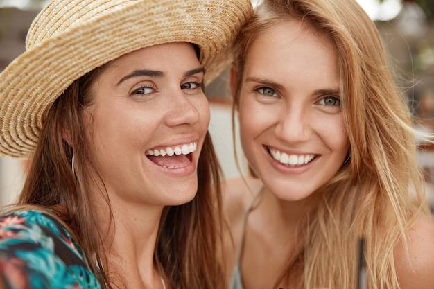 Снимок крупным планом красивых женщин с широкими улыбками, с позитивным выражением лица, счастливыми встретиться вместе. улыбающаяся молодая брюнетка в соломенной шляпе проводит летние каникулы с другом
