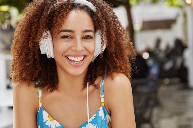 ヘッドフォンでポピュラー音楽を楽しんだり、暇な時間を過ごしたり、カフェテリアで友達を待ったりするので、気分が良い美しい幸せな巻き毛の黒い肌の女性のクローズアップショット。