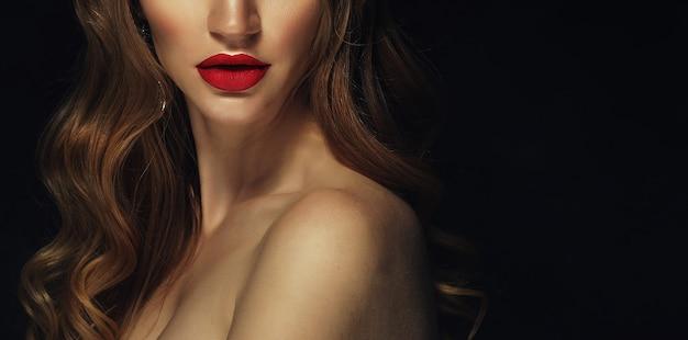 붉은 입술으로 아름 다운 여자 얼굴의 클로즈업 샷. 금발 곱슬 머리.