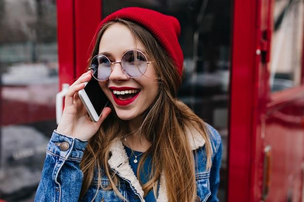 전화 통화하는 캐주얼 안경에 아름 다운 여자의 근접 샷.