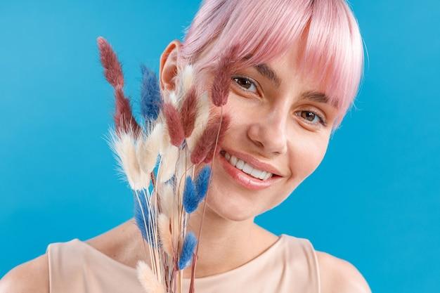 Крупным планом снимок красивой женщины с розовыми волосами, улыбаясь в камеру, держа в руке сушеные цветы