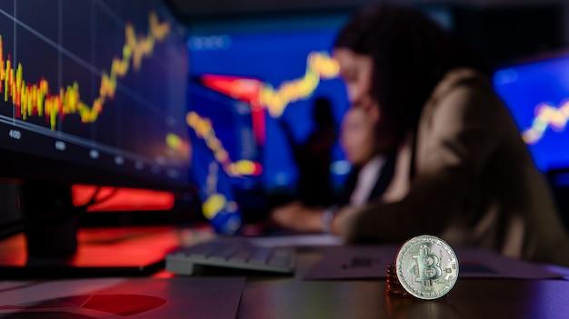Крупным планом снимок биткойн-криптовалюты перед азиатским брокером-трейдером-инвестором на портативном компьютере.