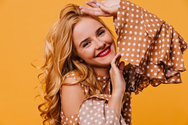 갈색 드레스에 행복 한 유럽 여자의 클로즈업 샷. 노란색 벽에 서있는 blithesome 소녀를 웃 고있다.