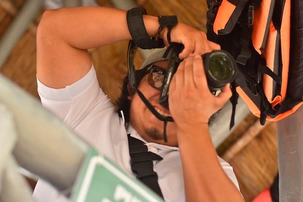Slr을 손에 들고 있는 소년 사진가의 클로즈업 샷