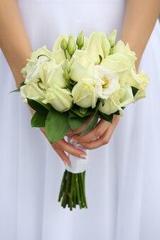 緑のバラと美しいウェディングブーケを保持している花嫁の手のショットを閉じる