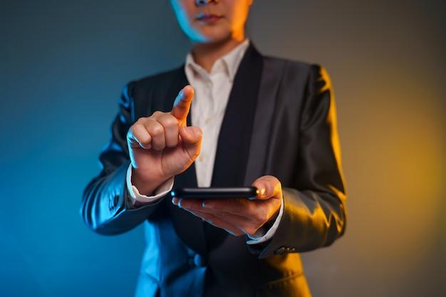 Закройте вверх по выстрелу деловой женщины, держащей смартфон в черном костюме. элегантный смарт на черном фоне.