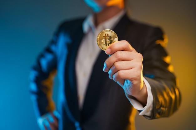 背景に分離された黄金のコインを保持している黒いスーツを着たビジネス女性のショットを閉じます。
