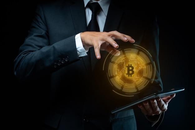 ビットコインシンボルホログラム効果を持つタブレットを保持している黒いスーツを着たビジネスマンのクローズアップショット。
