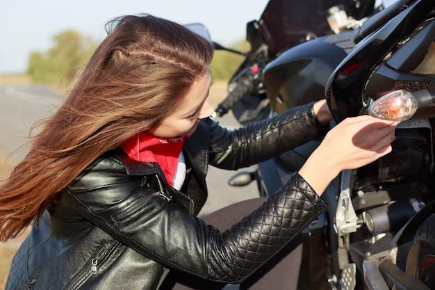 忙しい女性のバイクのクローズアップショットは、壊れた輸送の問題を解決しようとし、バイクに乗って、黒い革のジャケットを着ています。