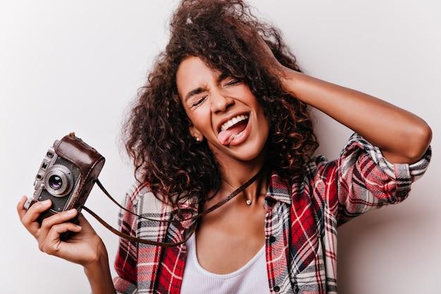 촬영 후 장난하는 평온한 여성 촬영 작가의 클로즈업 샷. 카메라 화이트에 재미있는 얼굴을 만드는 행복 한 아프리카 아가씨.