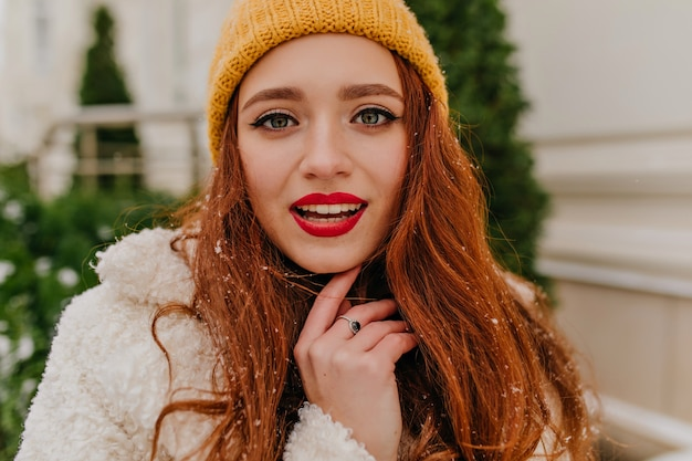 長い生姜髪ののんきな女性のクローズアップショット。冬にポーズをとるjocund女性の屋外写真。