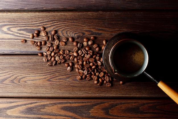 Крупным планом турка с кофейными зернами на деревенском деревянном столе, вид сверху