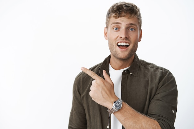 ブロンドの髪、剛毛、青い目を持つカリスマ的な印象的な魅力的な男性のクローズアップショットは、灰色の壁に対して左上隅を指している興奮した好奇心旺盛な笑顔で質問をします