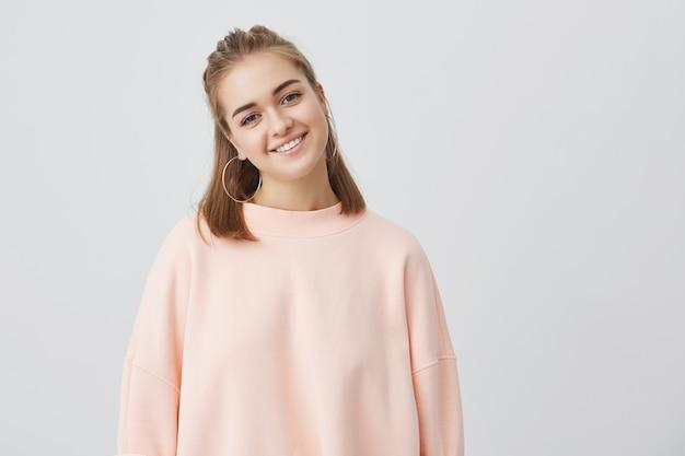 Крупным планом выстрел очаровательной кавказской девушки со светлыми прямыми волосами, одетый в розовый, нежно глядя, улыбаясь, слушая интересные истории и хорошие новости. нежная, красивая, молодая.