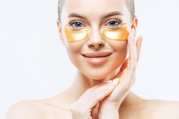 Снимок крупным планом очаровательной нежной молодой женщины, наносящей золотые коллагеновые пятна на свежую кожу лица