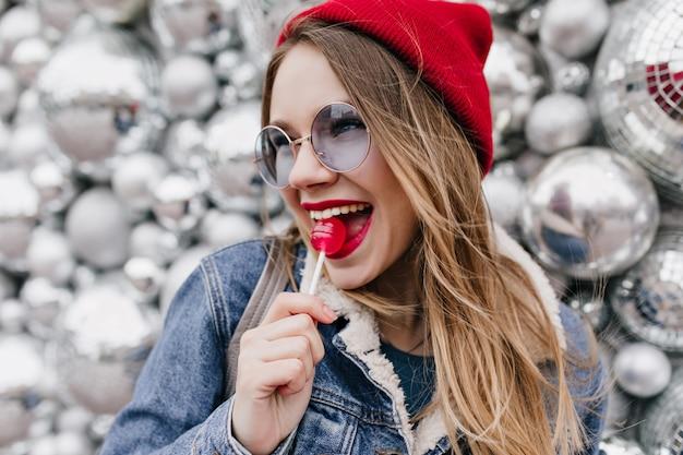 赤いキャンディーとの写真撮影中に楽しんでいる魅力的な若い女性のクローズアップショット。きらめく壁にロリポップを舐めているデニムジャケットの魅力的な女の子。
