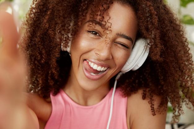 陽気なアフリカ系アメリカ人女性のクローズアップショットは、ヘッドフォンで快適な音楽を聴き、自分撮りのポーズをとり、機嫌が良いです。 10代の黒い肌の女の子が近代的なデバイスで自分自身をエンタナティン