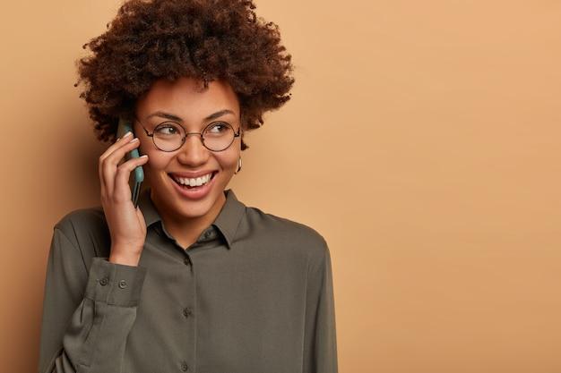 陽気なアフロアメリカ人女性のクローズアップショットは陽気な電話での会話をしていて、広く笑顔で、しんみりとどこかに見えます
