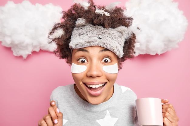 陽気な若い女性のクローズアップショットは、カメラの飲み物に大きな驚きを持って見つめています朝のさわやかな飲み物は、目の下の額の眠りのスーツの美容パッドにsleepmaskを着ています