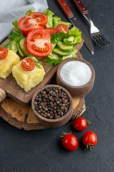 まな板の上に刻んだ新鮮な野菜のチーズと、黒い表面にセットしたスパイス カトラリーの接写