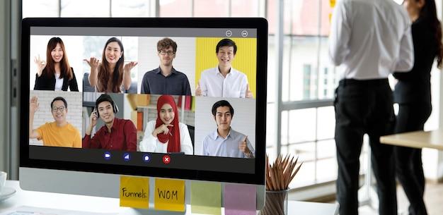 Закройте снимок экрана монитора компьютера, показывающего коллегу и клиента на глобальной многонациональной видеоконференцсвязи в офисе компании. неизвестный до неузнаваемости персонал отдыхает.
