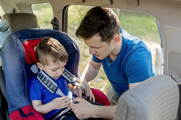 息子が車の座席にベルトを締めるのを手伝う集中した父親のクローズアップショット。子供の輸送の安全。