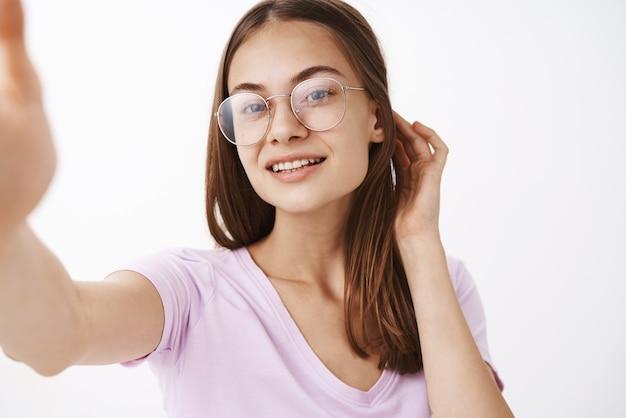 自信を持って見栄えの良い官能的でフェミニンな若い女性の耳の後ろで髪をフリックフワフワ笑顔笑顔で楽しくきれいなきれいな肌の外観を楽しんでいるセルフィーを取って笑顔