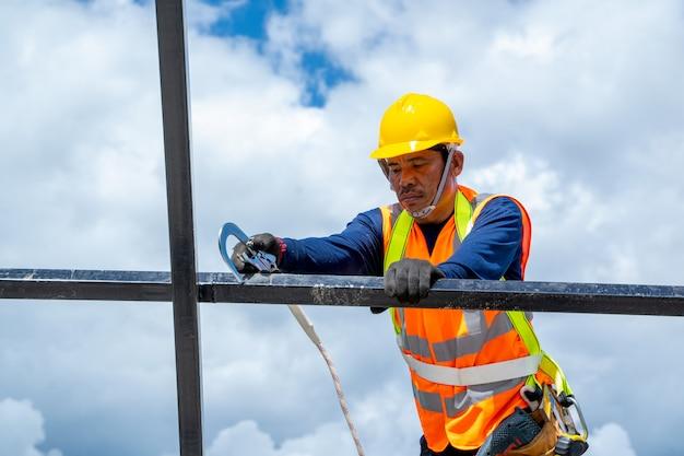 새 지붕 위에 높이 작업 안전 하네스를 착용하는 건설 노동자의 총을 닫습니다.