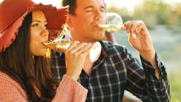 白ワインのグラスを手に持って優しい瞬間を持っている太陽フレアのカップルのクローズアップショット。