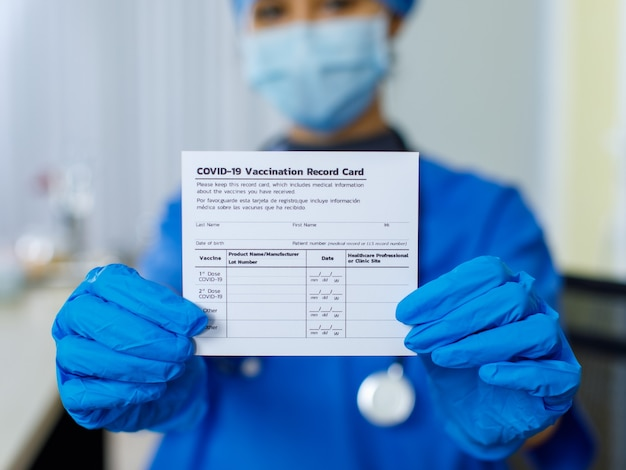 코비드-19 예방 접종 기록 카드 인증서 여권 용지의 클로즈업 샷이 흐릿한 배경에서 파란색 병원 유니폼 얼굴 마스크와 고무 장갑을 착용하는 의사의 손에 보여주고 제시했습니다.