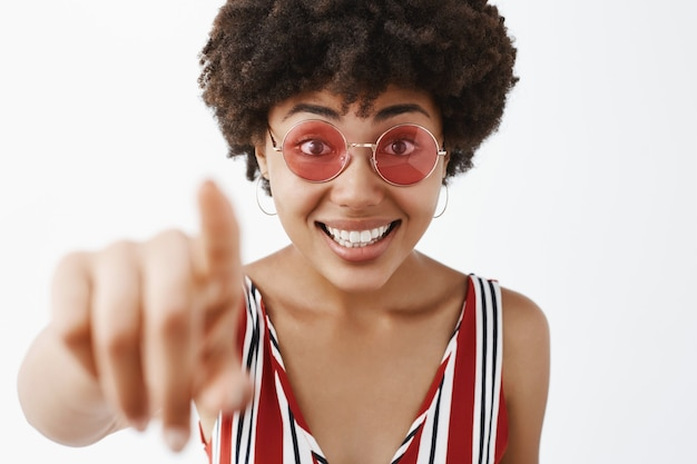 Снимок крупным планом любопытной, возбужденной и удивленной привлекательной счастливой темнокожей женщины с вьющимися волосами в полосатой блузке и солнцезащитных очках, указывающей указательным пальцем и улыбающейся, находящейся под впечатлением