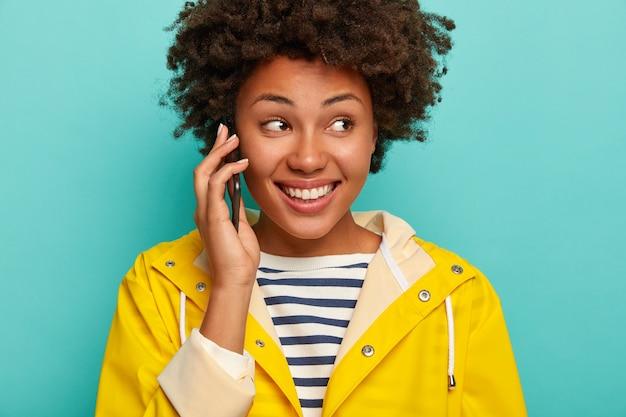 巻き毛の女性のクローズアップショットは幸せな表情をしており、陽気な話をするために親友を呼び出し、黄色の防水レインコートを着て、脇に集中し、青い背景に対して屋内に立っています。