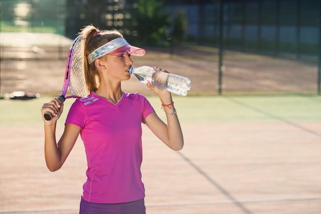 하드 테니스 훈련 일몰 후 플라스틱 병에서 스포티 한 모자 식 수에 귀여운 어린 소녀의 총을 닫습니다.