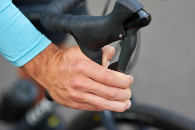 ハンドルバーで自転車のブレーキを押すサイクリストの手のクローズアップショット