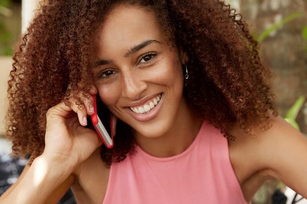 アフロの髪型を持つ暗い肌の美しい女性のクローズアップショットは、携帯電話で会話しています。アフリカ系アメリカ人の若い女性がボーイフレンドとデジタル携帯電話について話し、過ぎ去った日について語ります