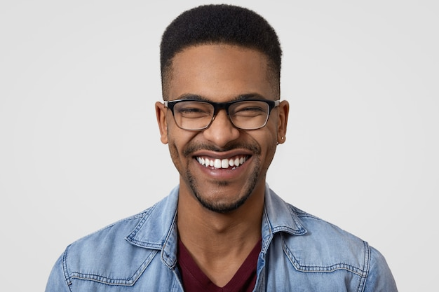 広い歯を見せる笑顔、白い歯、眼鏡、短い巻き毛、面白い冗談で笑う暗い肌の男のショットを閉じる