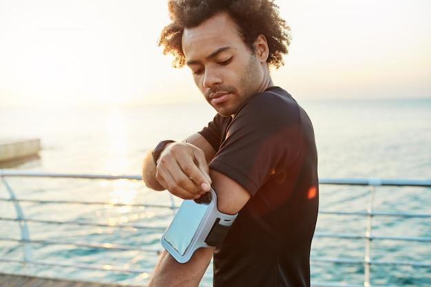 モバイルアームバッグを修正する浅黒い肌の男性アスリートのクローズアップショット。海の後ろでの朝の屋外トレーニングセッション。スポーツ、テクノロジー、レジャーのコンセプト。