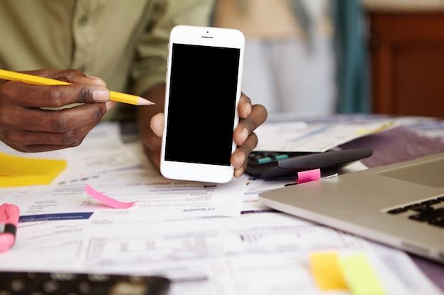 空白の画面の携帯電話と鉛筆を保持している浅黒い肌の男の手のショットを閉じる