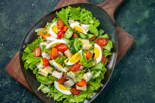 黒緑のミックス色の背景に木製のまな板に多くの新鮮な食材とおいしいサラダのクローズアップショット