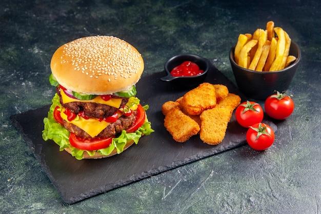 黒い表面に暗い色のトレイ トマトにおいしいサンドイッチとチキン ナゲット ケチャップのクローズ アップ ショット