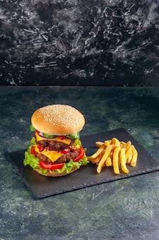 검은 색 표면에 어두운 색 트레이에 맛있는 샌드위치와 감자 튀김의 총을 닫습니다