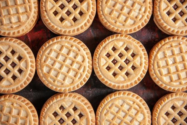 여유 공간이 있는 혼합 색상 배경에 행으로 배열된 맛있는 설탕 쿠키의 클로즈업 샷