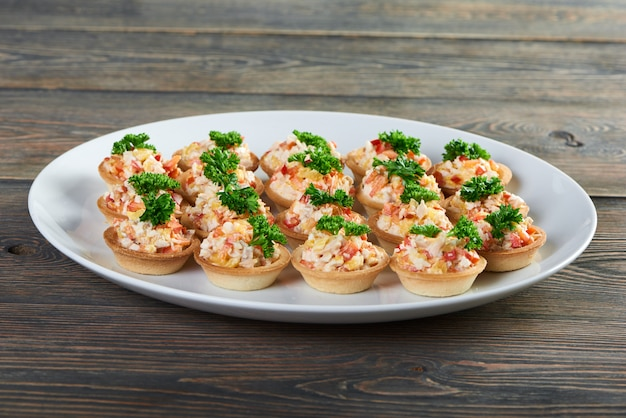 Закройте снимок вкусных тарталеток, наполненных салатом, украшенным зеленью, подается на белой керамической тарелке на деревянном столе в меню местного ресторана, где подают закуски.