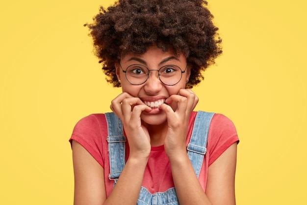 필사적으로 화가 난 아프리카 계 미국인 여성이 손톱을 물고, 불쾌하고 긴장된 표정을 짓고, 부정적인 뉴스에 반응하고, 부담없이 옷을 입고, 노란 벽 위에 고립 된 샷을 닫습니다.