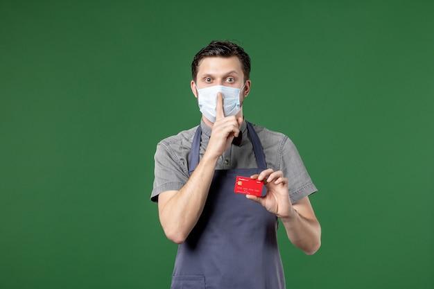 의료 마스크를 착용하고 녹색 배경에 침묵 제스처를 만드는 은행 카드를 들고 있는 단호한 남성 웨이터의 클로즈업 샷